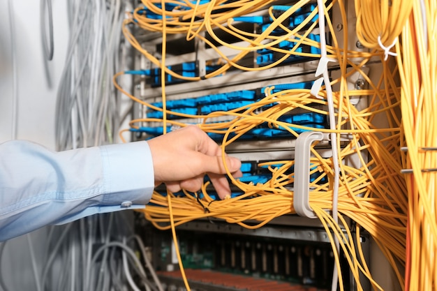 Hand of young engineer connecting cables in server room