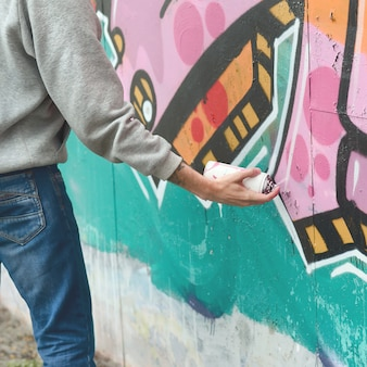 Hand of a young guy in a gray hoodie paints graffiti in pink and