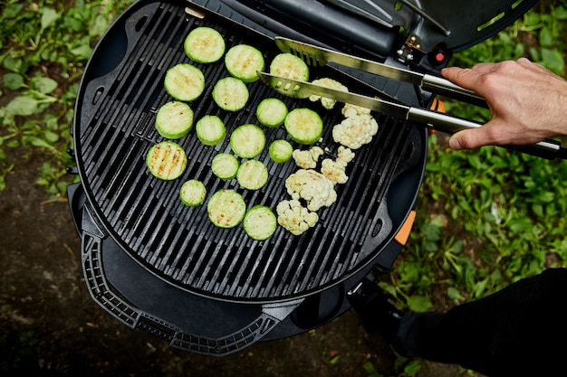 Hand of young man grilling zucchini vegetable on huge gas grill .