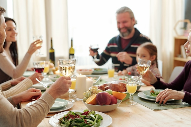 Hand of young man holding glass of wine over served table during toast at festive family dinner on thanksgiving day