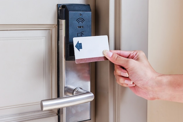 Hand young man holding a keycard in front of the electronic sensor of a room