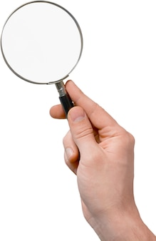 Hand of young man holding magnifying glass