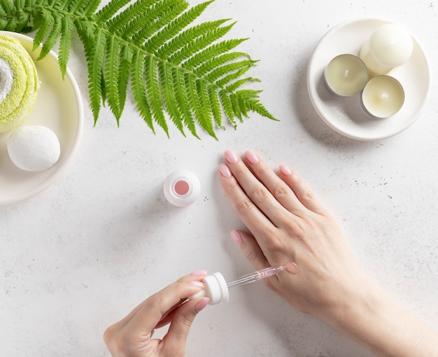 Hand of a young woman applying serum (collagen moisturizer, hyaluronic acid, vitamin c) to the skin. skin care routine. white wall with candles and green leaf. top view.