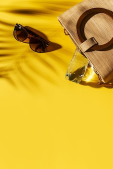 물 병, 열대 잎 그림자, 크리 에이 티브 파스텔, 해변 휴가 개념, 복사 공간, 평면도와 밝은 노란색 배경에 핸드백과 안경