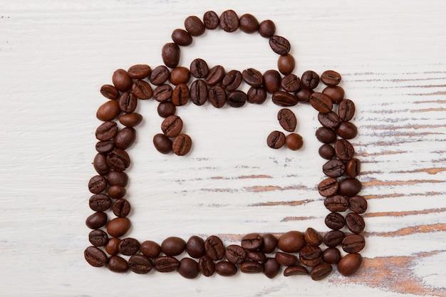 흰색 나무에 커피 콩으로 만든 핸드백. 갈색 알갱이가 가방 모양으로 배열되어 있습니다.