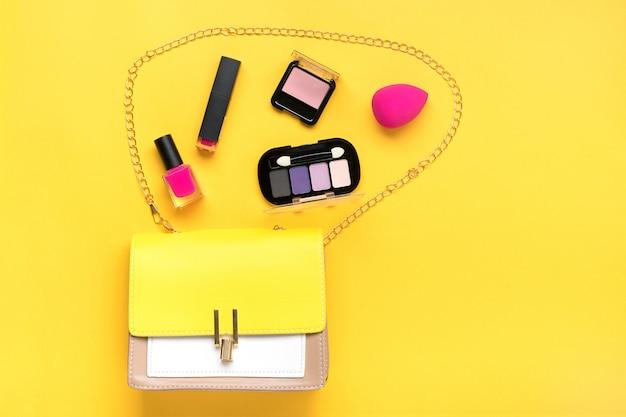 Сумочка, набор профессиональной декоративной косметики, черные инструменты для макияжа и аксессуар модного розового цвета на желтом фоне