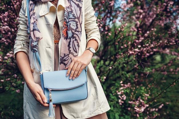 ハンドバッグ。スタイリッシュなバッグを押しながらトレンディな服を着ている女性。
