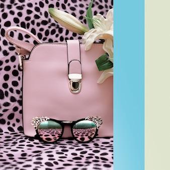 호피 무늬 배경에 핸드백과 패션 세련된 선글라스. 파스텔 컬러 트렌드