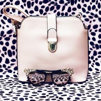 호피 무늬 배경에 핸드백과 패션 세련된 선글라스.