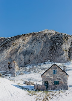 高い岩と美しい澄んだ青い空を背景に手作りの灰色の石造りの家