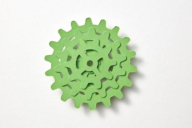 柔らかい影、コピースペースと白い背景の上のスタックの形で緑色の紙からマシンギアのハンドカーフトセット。上面図。