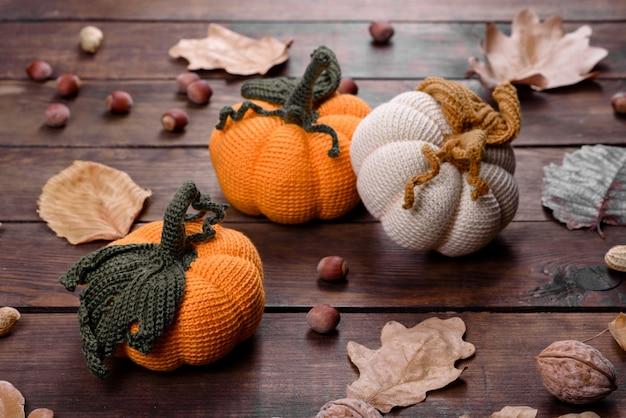 Осенний натюрморт ручной работы: вязаные тыквы и листья на деревянном фоне. украшение хэллоуина и дня благодарения