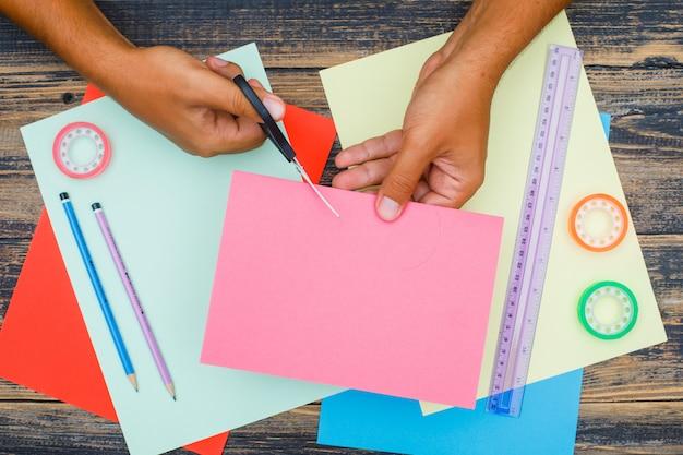 Концепция ручной работы с правителем, ленты, карандаши на деревянных фоне плоской планировки. человек резки бумаги.