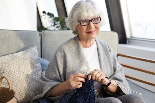 Handcraft, hobby, age and retirement concept. elegant beautiful elderly female with wrinkles and short gray hair enjoying leisure time, sitting in living room and knitting stylish scarf for herself