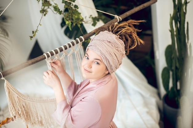 手作り。マクラメを織り、前向きに見える帽子の若い女性