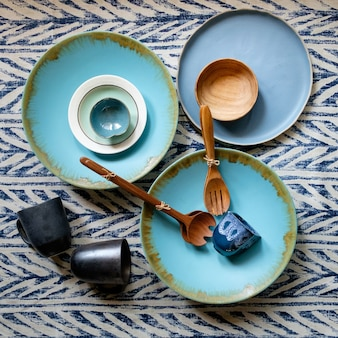 Handcrafted ceramic and wooden tableware with cutlery on blue twill pattern fabric