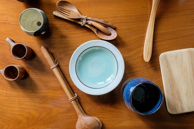 Handcrafted ceramic and wooden tableware with cutlery on wooden background, top view