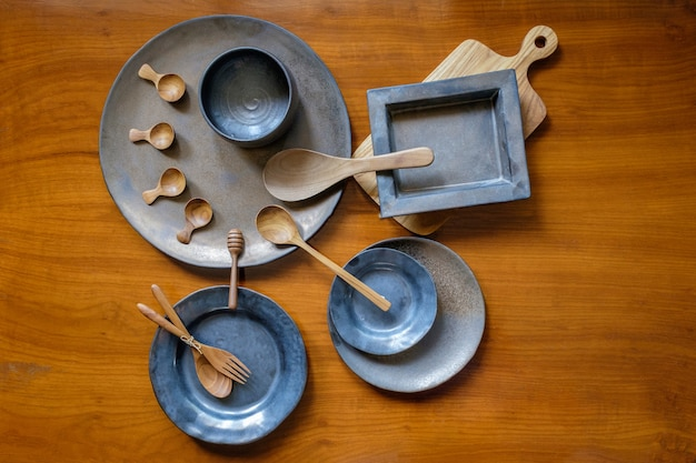 Handcrafted ceramic and wooden tableware with cutlery on wooden background