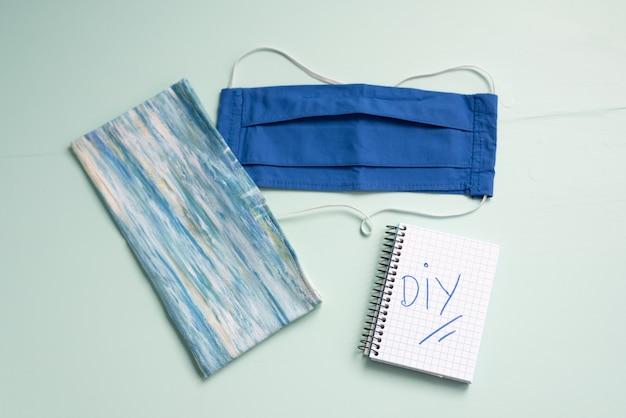 Diyで書かれたメモ帳付きの手作りフェイスマスクとファブリックバッグ
