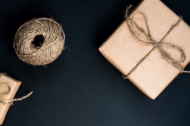 Handcrafted gift box wrapped in craft paper with rope and bow. top view, flat lay