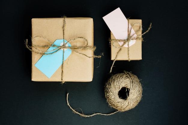クラフト紙に包まれた手作りのギフトボックスに、青とピンクの紙カードタグ、ロープ、装飾用の木製の洗濯はさみが付いています。