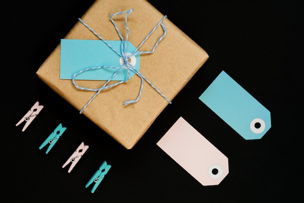 クラフトペーパーに包まれた手作りのギフトボックスに、青とピンクの紙カードタグ、ロープ、木製の洗濯はさみを飾ります。
