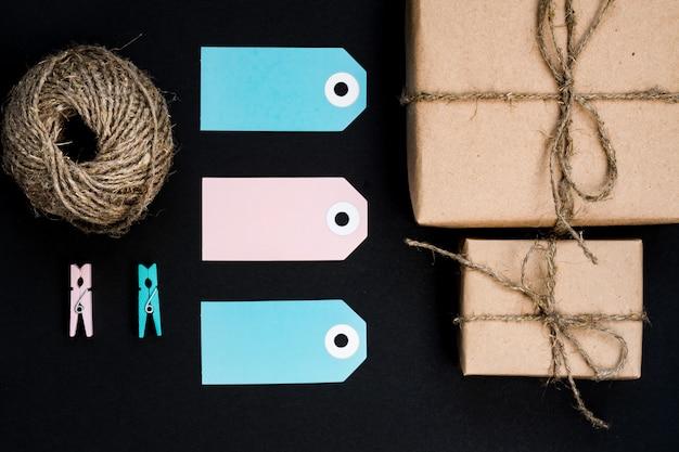 青い紙カードタグ、ロープ、装飾用の木製洗濯はさみを備えたクラフト紙に包まれた手作りのギフトボックス。