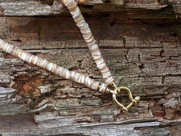 Перламутровое колье ручной работы из полированных деталей в подарок женщине на деревянном фоне