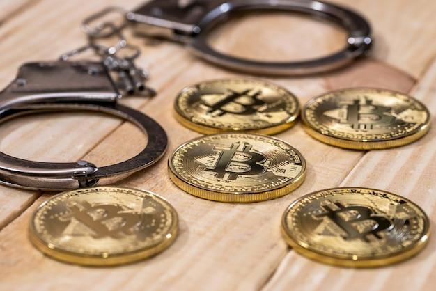 手錠とゴールドのビットコイン。犯罪の概念