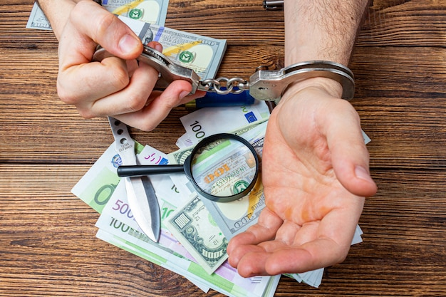 Handcuffed hands on a money banknotes