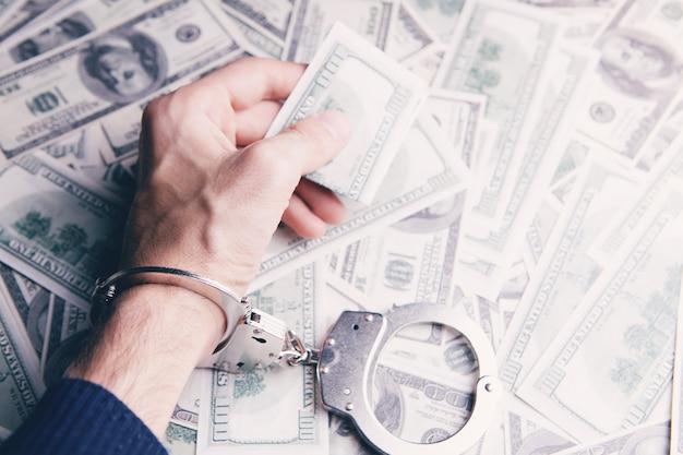 Handcuffed man holding money