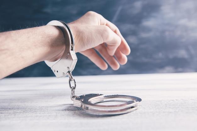 Handcuffed man of woodne table