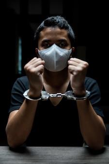 男性囚人は囚人に手錠をかけられ、暗い刑務所で手錠をかけられていた。