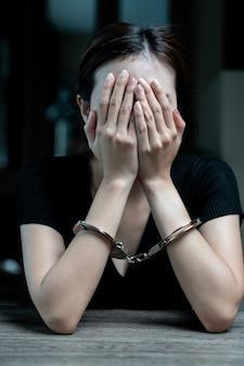 囚人に手錠をかけられた女性囚人は、暗い刑務所で手錠をかけられていた。