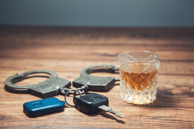Handcuffes and car key with glass of drink on the table