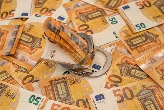 수갑과 유로 지폐. 부패와 뇌물 수수 개념