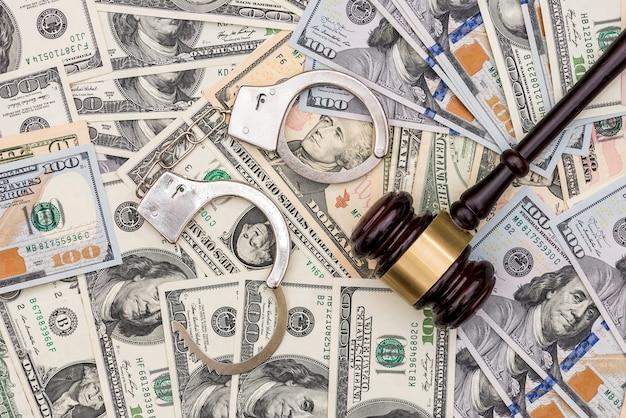 Наручники и молоток судьи на поверхности долларовых банкнот