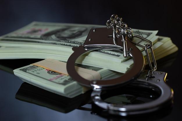 暗闇の中の手錠とお金。ビジネス詐欺と腐敗の概念
