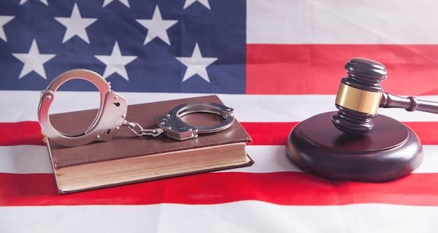 手錠、本、アメリカの国旗の背景にジャッジガベル