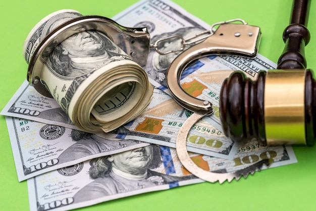緑の背景に手錠、ドル紙幣、裁判官のガベル