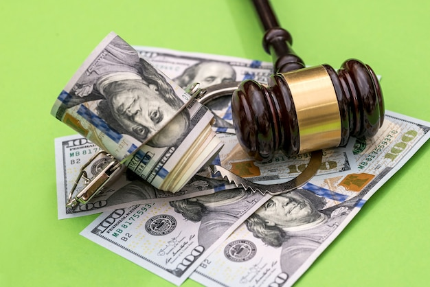 Handcuffs, dollar notes and judge's gavel on green surface