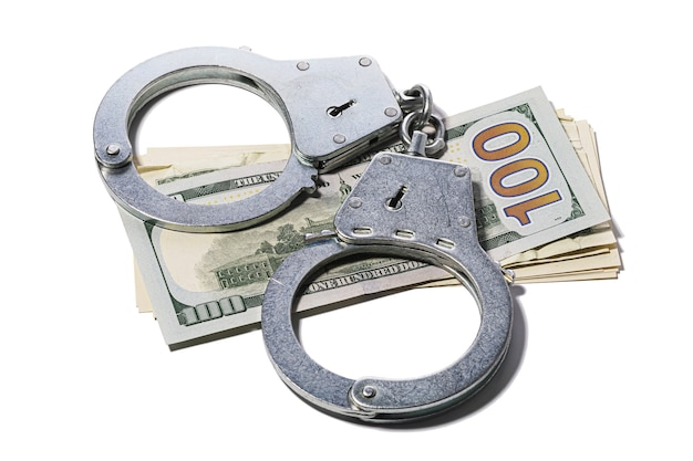 Handcuffs on dollars isolated on white background concept on the topic of fraud with foreign exchange transactions