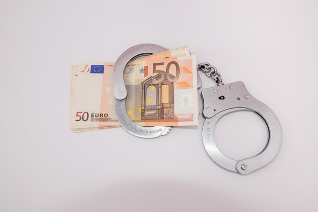 Handcuffs and euro banknotes on white. crime concept.