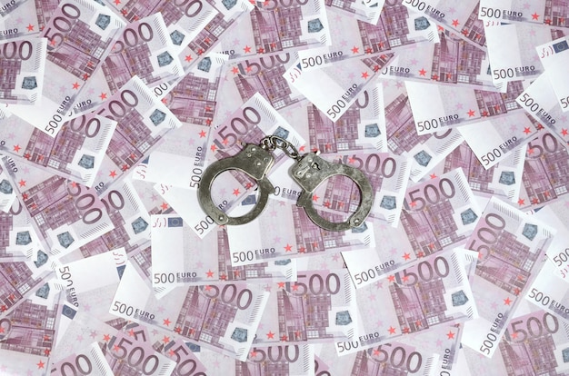 Handcuffs on five hundred euros background.