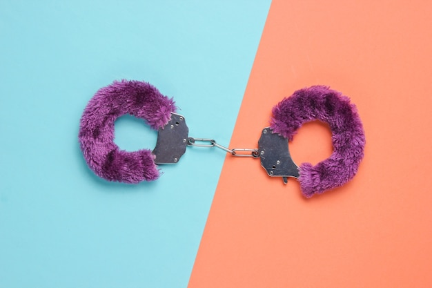Наручники для секс-игр на цветном фоне. сексуальная бдсм игрушка. концепция любви.