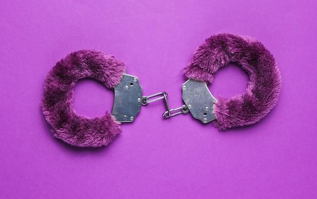 紫色の背景にセックスゲームの手錠。性的な緊縛おもちゃ。フェチ、エロティックなコンセプト。