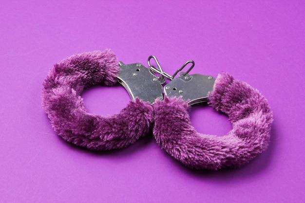 Наручники для секс-игр на фиолетовом фоне. сексуальная бдсм игрушка. фетиш, эротическая концепция.