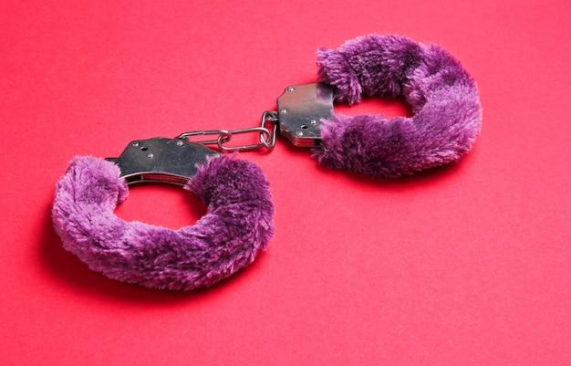 赤い背景のセックスゲームの手錠。性的な緊縛おもちゃ。フェチ、エロティックなコンセプト。