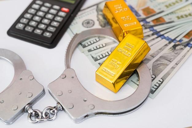 Наручники, золотые слитки с долларами и калькулятор на белом фоне