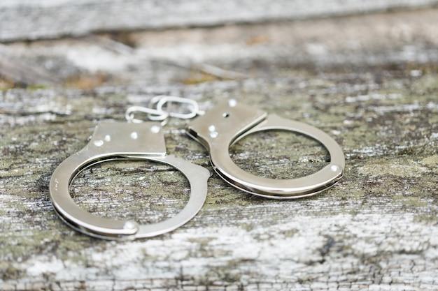 На старом бетонном полу лежат наручники. фото высокого качества